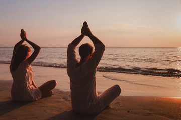 yoga on the beach, couple silhouettes practice meditation and breathing exercises, lotus position