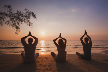 yoga group on the beach, silhouettes of people meditating in lotus position at sunset, meditation and breathing exercises