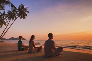yoga retreat on the beach at sunset, silhouettes of group of people meditating