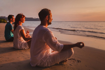 group meditation, people practicing yoga on the beach, relaxation and breathing excercises