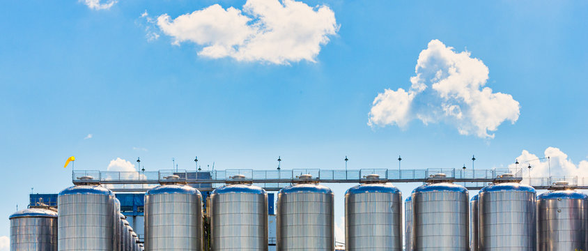 Fermentation tanks for beer with beautiful sky.
