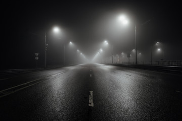 Foto op Canvas Nacht snelweg Foggy misty night road illuminated by street lights
