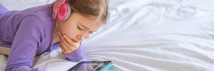 Young teenager girl in pink headphones with tablet device in home lying on white bed. Stock photo banner for any purposes.