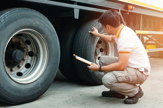 Truck driver holding clipboard inspecting safety check a truck tires,  vehicle maintenance checklist a semi truck