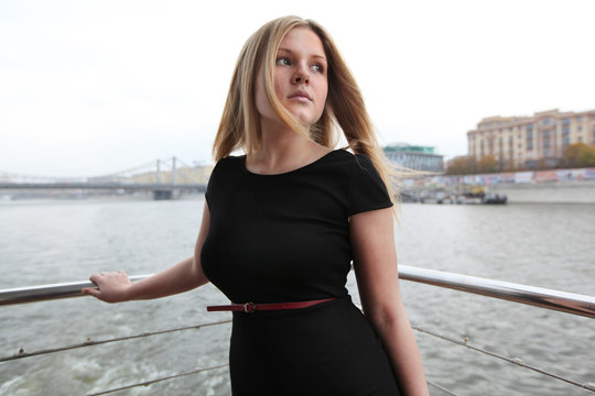 Beautiful blonde in a black dress on a ship in the city
