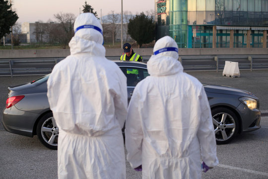 Medical staff check a passenger in a car for coronavirus (COVID-19) at the border crossing with Italy in Vrtojba