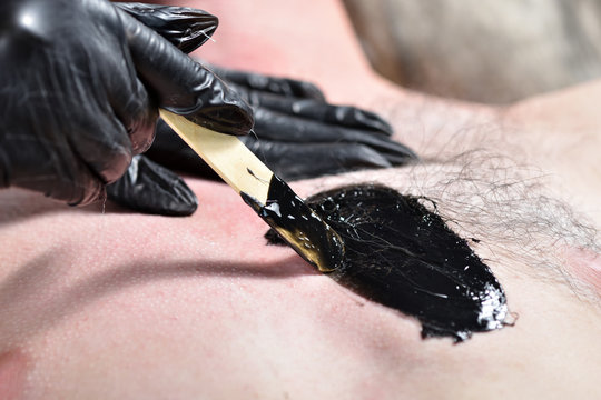 Hairy male chest and black wax for depilation. Male waxing