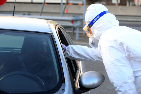 Medical staff checks a passenger in a car for coronavirus (COVID-19) at the border crossing with Italy in Vrtojba
