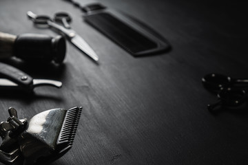 On a black dusty surface are old barber tools. Vintage manual hair clipper comb razor shaving brush shaving brush hairdressing scissors. black monochrome