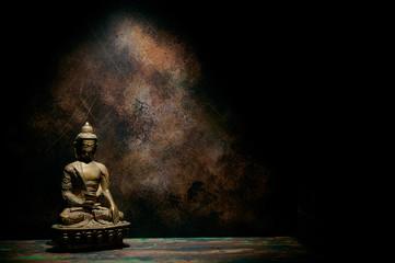 Statuette of Buddha on a dark background.