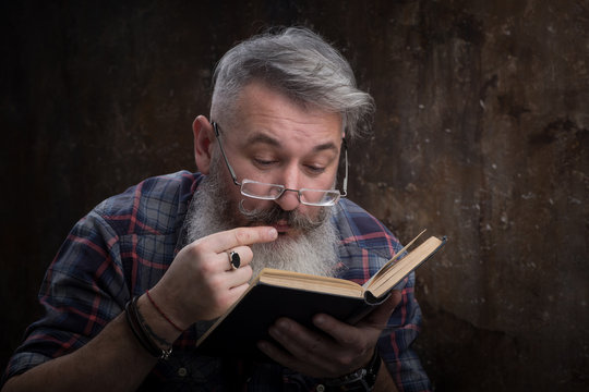 Portrait of a gray-haired bearded man with glasses reading a book, on the cover a Russian inscription M. Gorky, selective focus