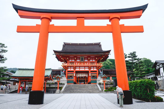 Oldman form back and Great Torii gate and the Romon Gate at Fushimi Inari taisha shrine, Kyoto, Japan