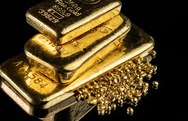 Several gold bars of different weight and a pile of pure gold granules on a mirror dark background.