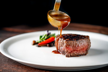 Photo sur Toile Steakhouse Grilled beef tenderloin steak on a white platter is served with demiglas sauce