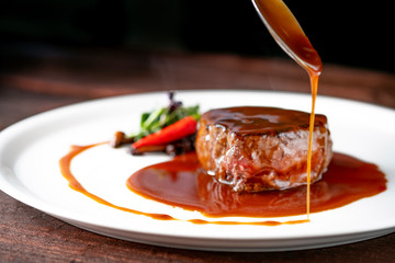 Foto op Canvas Steakhouse Grilled beef tenderloin steak on a white platter is served with demiglas sauce