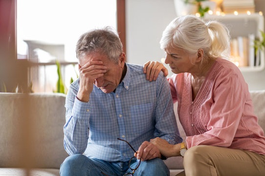 Senior woman consoling her husband at home