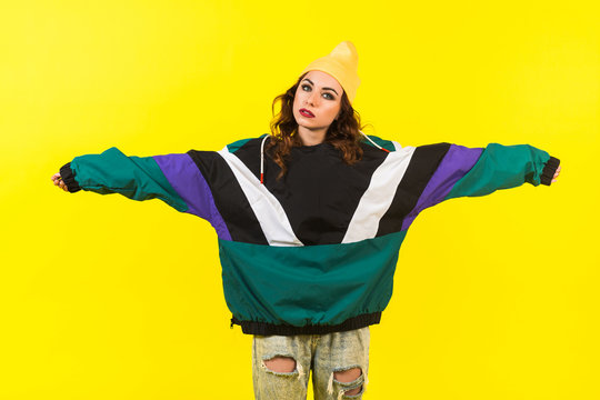 Modern beautiful girl in oversized sports jacket, hat and jeans, Billie Eilish style, back in the 90s, 2000s. Posing in the studio on a yellow background.