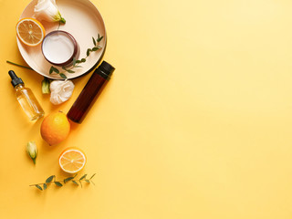 flatlay composition with cream, lotion, oil, flower, citrus and eucalyptus on yellow background. Concept beauty natural vitamin cosmetic product, skin care, copyspace, top view