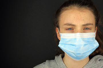 Teenage girl with sore eyes wearing a face mask stopping the spread of the coronavirus concept.