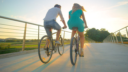LOW ANGLE: Unrecognizable couple riding their bikes across an overpass at sunset Fotobehang
