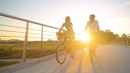 LOW ANGLE: Young woman smiles while riding her bike with her boyfriend at sunset Fototapete