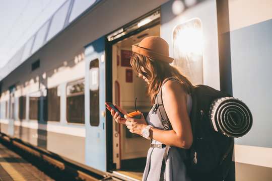 Railroad theme. Beautiful young woman with a backpack uses the phone while standing near the railroad train on the platform. Cheap travel