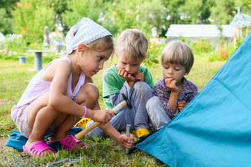 cute little boys and girl toddlers help set up a camping tent. family with little children have fun spending summer holidays in nature outdoor Fototapete
