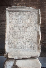 Ancient marble tablet engraved with the Venantius incription inside the Colosseum in Rome, Italy. The inscription commemorates the restoration of the Colosseum's podium a