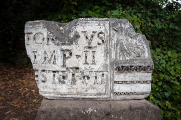 Broken marble stone with latin inscription on display at the Forum, Rome