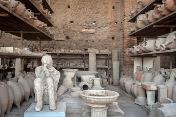 Plaster cast of the body of 'the Muleteer' surrounded by broken pottery in the former Forum Granary at Pompeii, Italy