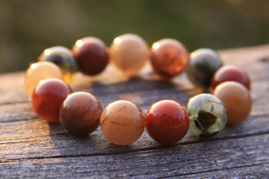 Round gemstone beads in circle on wood shining in sunlight