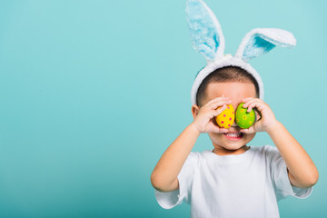 child boy wearing bunny ears and white T-shirt, standing to holds easter eggs instead of eyes