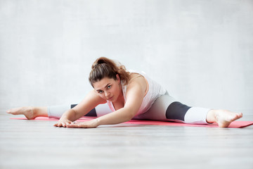 Lovely woman doing stretching or yoga exercise