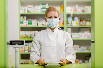 Foto op Canvas Apotheek Pleasant professional young female pharmacist with surgical mask smiling