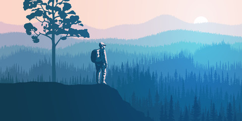 Wall Mural - A tourist with a backpack on a rock meets dawn. Hills and mountains covered by forest, taiga. Morning haze, the light of sunrise.