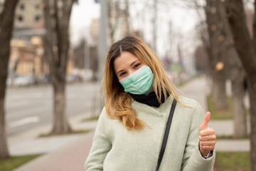 woman in medical mask in a European city showing thumbs up Fotobehang