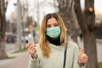 woman in mask feeling protecting from the coronavirus, Covid2019 holding hands sanitizer showing like thumbs up fingers gesture Wall mural