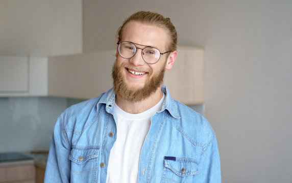 Portrait young happy bearded millennial man,student guy hipster wear glasses own house new flat cosy modern studio apartment smile confident look at camera kitchen background home real estate concept.