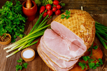 Dinning table with whole baked and sliced ham, vegetables and spice.