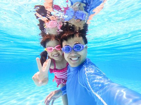 asian family in swimming pool