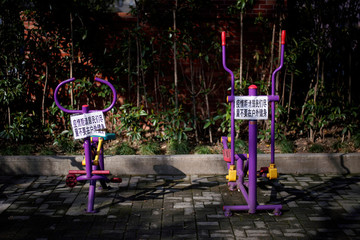 Signs advising residents to avoid exercising outdoor during the novel coronavirus outbreak are seen on exercise machines at a park in Shanghai