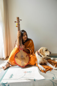 Dog sitting beside her owner while the woman playing music on her tambura,