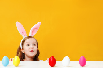 Easter concept. Delighted surprised happy child in the ears of a bunny on a yellow background. Little girl is looking from the table at copy space for text