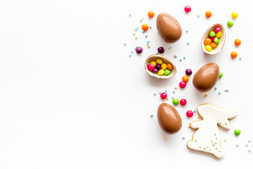 Easter sweets frame. Chocolate eggs and bunny gingerbread on white background top-down frame copy space