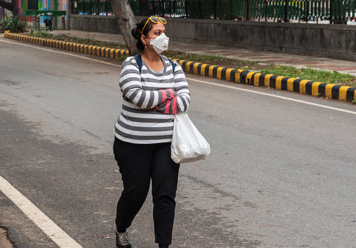 An Indian girl walking on the road in Delhi, lady wearing an N 95 mask in India after the Global spread of corona virus pandemic disease in asian countries. Air pollution and Covid 19 concept.