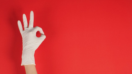 A Okay hand sign with gloves in left hand on red background. Wall mural