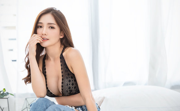 Portrait of asian woman in black lace bra lingerie underwear boudoir. Beauty smiling asian girl applying lotion on shoulder arm skin in her morning routine. Sexy girl modern asia lifestyle concept
