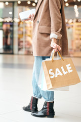 Close-up of unrecognizable woman in long jacket walking with shopping bags while enjoying big sale in mall