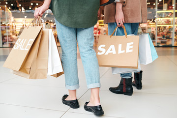 Close-up of unrecognizable woman with paper bags going shopping with friend in mall
