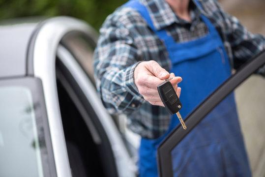 Mechanic delivering car keys after car engine checking